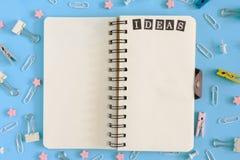 Öffnen Sie Notizbuch auf den Frühlingen mitten in der Verwirrung des Briefpapiers Aufschrift-Ideen auf der weißen Seite clips stockbild