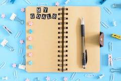 Öffnen Sie Notizbuch auf Frühlingen mit einer Aufschrift meine Ziele Briefpapier razrosannye auf einem blauen Hintergrund Kanzlei lizenzfreie stockfotos