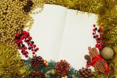 Öffnen Sie Notizbuch, ein Blatt Papier mit Weihnachtsspielwaren, Beeren und gezierte Zweige auf Goldhintergrund Stockfotografie