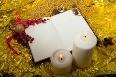 Öffnen Sie Notizbuch, ein Blatt Papier mit Weihnachtsspielwaren, Beeren und gezierte Zweige auf Goldhintergrund Stockbilder