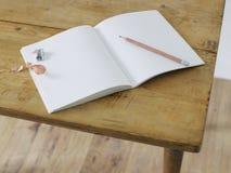 Öffnen Sie Notizbuch mit Bleistift und Bleistiftspitzer auf Tabelle erhöhter Ansicht Stockfoto