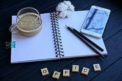 Öffnen Sie Notizbuch mit Bleistiften eines Tasse Kaffees und einem Smartphone auf dem Tisch und ein Wort von hölzernen Buchstaben Stockbilder