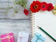 öffnen Sie Notizbuch mit Blume, Geschenkboxen, Bleistift auf hölzernem Hintergrund Stockbild