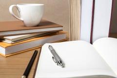 Öffnen Sie Notizbuch mit Buch und Kaffeetasse Stockfotos