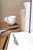 Öffnen Sie Notizbuch mit Buch und Kaffeetasse Stockbilder