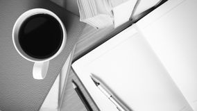 Öffnen Sie Notizbuch mit Buch- und Kaffeetasseschwarzweiss-Farbe zu Lizenzfreie Stockfotos