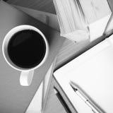 Öffnen Sie Notizbuch mit Buch- und Kaffeetasseschwarzweiss-Farbe zu Stockfoto