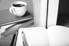 Öffnen Sie Notizbuch mit Buch- und Kaffeetasseschwarzweiss-Farbe zu Lizenzfreies Stockbild
