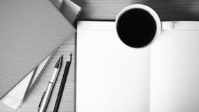 Öffnen Sie Notizbuch mit Buch- und Kaffeetasseschwarzweiss-Farbe zu Stockbilder