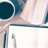 Öffnen Sie Notizbuch mit Buch- und Kaffeetasseweinleseart Stockfotos