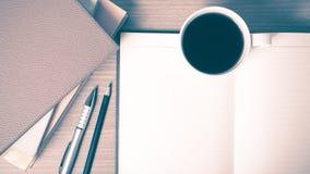 Öffnen Sie Notizbuch mit Buch- und Kaffeetasseweinleseart Stockbilder
