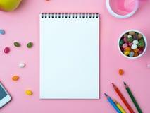 Öffnen Sie Notizbuch mit einem sauberen weißen Blatt, Bonbons, Handy, Zeichenstift, Dekorationen auf einer rosa hellen Tabelle Stockbild