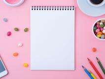 öffnen Sie Notizbuch mit einem sauberen weißen Blatt, Karamell, Lutscher, Handy, Zeichenstift, Tasse Kaffee, Dekorationen auf ein Lizenzfreies Stockfoto