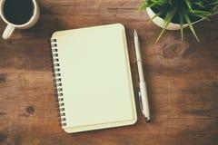 öffnen Sie Notizbuch mit Leerseiten nahe bei Tasse Kaffee Stockfoto