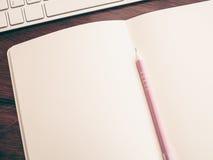 Öffnen Sie Notizbuch mit rosa Stift und Teil der Tastatur Lizenzfreies Stockfoto