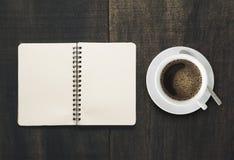 Öffnen Sie Notizbuch mit Tasse Kaffee auf schwarzem hölzernem Schreibtisch Seite Empt Stockfoto