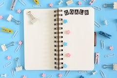 Öffnen Sie Notizbuch mitten in der Verwirrung des Briefpapiers Aufschrift-Ziele auf der weißen Seite Klipp, kanzleimäßige Knöpfe  lizenzfreie stockbilder