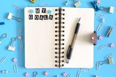 Öffnen Sie Notizbuch mitten in der Verwirrung des Briefpapiers Aufschriften meine Ziele auf einer weißen Seite Klipp, Wäscheklamm stockbild