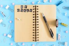 Öffnen Sie Notizbuch mitten in der Verwirrung des Briefpapiers Aufschriften meine Ziele auf einer weißen Seite Klipp, Wäscheklamm stockfoto