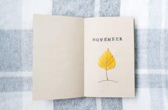 Öffnen Sie Notizbuch- und Birkenblatt auf dem Tisch november Stockbild
