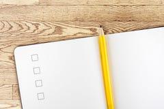 Öffnen Sie Notizbuch und gelben Bleistift auf Holztisch, Draufsicht, Templa Lizenzfreie Stockfotos