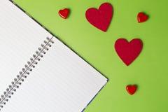 Öffnen Sie Notizbuch und rote Herzen auf Grünhintergrund Roter heart-shaped Schmucksachegeschenkkasten und eine rote Spule auf ei Stockfotos