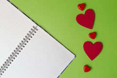 Öffnen Sie Notizbuch und rote Herzen auf Grünhintergrund Roter heart-shaped Schmucksachegeschenkkasten und eine rote Spule auf ei Lizenzfreie Stockfotos