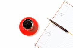Öffnen Sie Notizbuch und Tasse Kaffee auf einem weißen Hintergrund von oben Lizenzfreie Stockbilder