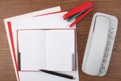 Öffnen Sie Notizbuch und weißes Telefon auf hölzerner Beschaffenheit Lizenzfreie Stockfotografie