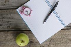 Öffnen Sie Notizbuchtagesordnung mit Zeitplan und kleiner rosa Uhr am 8:00 Stockbilder
