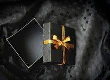 Öffnen Sie schwarze Geschenkbox mit goldenem Band Lizenzfreies Stockbild