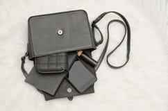 Öffnen Sie schwarze Tasche mit fallengelassenen Sachen, Notizbuch, Handy, Geldbeutel Der weiße Pelz auf Hintergrund, Draufsicht A Lizenzfreies Stockfoto