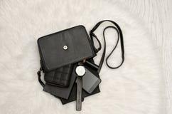 Öffnen Sie schwarze Tasche mit fallengelassenen Sachen, Notizbuch, Handy, Uhr, Geldbeutel und Lippenstift Der weiße Pelz auf Hint Stockbild