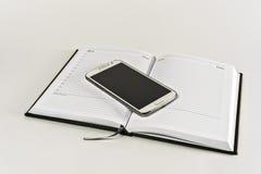 Öffnen Sie sich täglich auf Weiß und dem Lügen auf ihm ein Smartphone Stockbild