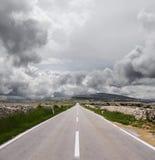 Öffnen Sie Straße und stürmische Wolken Stockfotografie