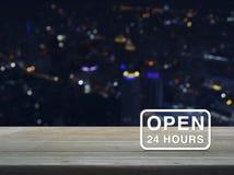 Öffnen Sie 24 Stunden Ikone auf Holztisch über buntem lig Nacht der Unschärfe Lizenzfreies Stockfoto