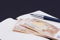 Öffnen Sie täglichen Planer mit Luxuskugelschreiber und einigen Eurobanknoten Stockfotos