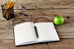 Öffnen Sie Tagebuch mit Leerseiten im Arbeitsplatznahaufnahmeapfel und im O Stockfotos