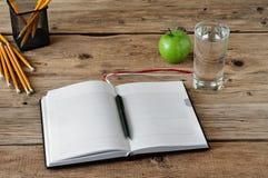 Öffnen Sie Tagebuch mit Leerseiten mit einem Glas Wasser Stockfotos