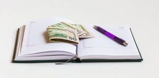 Öffnen Sie Tagebuch, um Arbeitsstunden mit Banknoten und einem Stift zu planen Stockbild