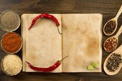 Öffnen Sie Weinlesebuch mit Gewürzen auf hölzernem Hintergrund Gesunde vegetarische Nahrung Rezept, Menü, Spott oben, kochend Stockfotos