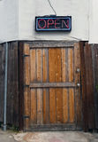 Öffnen Sie Zeichen über rustikaler hölzerner Tür Lizenzfreies Stockfoto