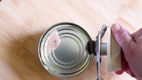 Öffnende Fischkonserven auf Holztischhintergrund stock video