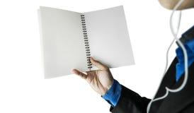 Öffnendes leeres Notizbuch auf einer tragenden Kopfhörerhand des Kerls, selektiver Fokus, lokalisiert auf weißem Hintergrund Lizenzfreie Stockfotos