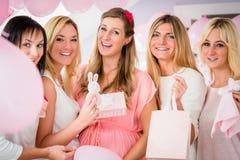 Öffnungspräsentkarton der schwangeren Frau auf Babyparty Lizenzfreies Stockfoto