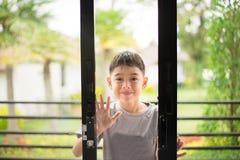 Öffnungstür des kleinen Jungen in das Haus Stockfotografie