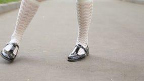 Ögla för närbild för ben för dansare` s Flicka som solo dansar jazzgungadans på trottoaren för fyrkant för stads` s Charlestondan stock video