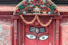 Ögon av Buddha på röd dörr i Nepal arkivfoto