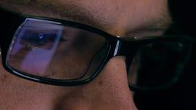 Ögon av den allvarliga unga mannen i svarta kantexponeringsglas genom att använda hans minnestavladator Skärm och finger som refl royaltyfria bilder