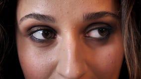 Ögon av den charmiga kvinnan med mörkt hår ler som håller ögonen på på kameran, tegelstenbakgrund arkivfilmer
